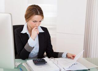 בחורה יושבת ליד שולחן עם מחשבון וערימת חשבונות