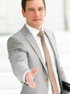 Handsome successful business man gesturing a hand shake